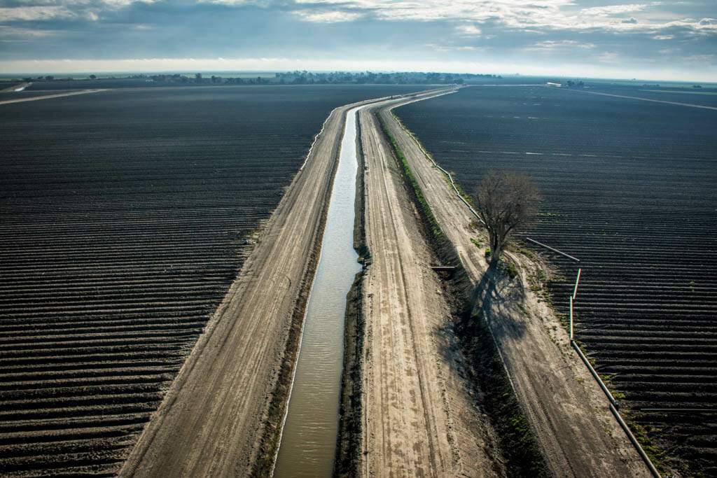 The Delta-Mendota Canal, part of the Central Valley Project, supplies water to the Bowles Farming Company's tomato fields. PVC pipes are laid out beside the canal for drip irrigation installation. Nearly half of the Bowles' several thousand acres have been converted from flood irrigation to drip. Although it costs about $1,500 an acre in materials and labor to install, it conserves a significant amount of water, which is critical to surviving a fourth year of California's historic drought.