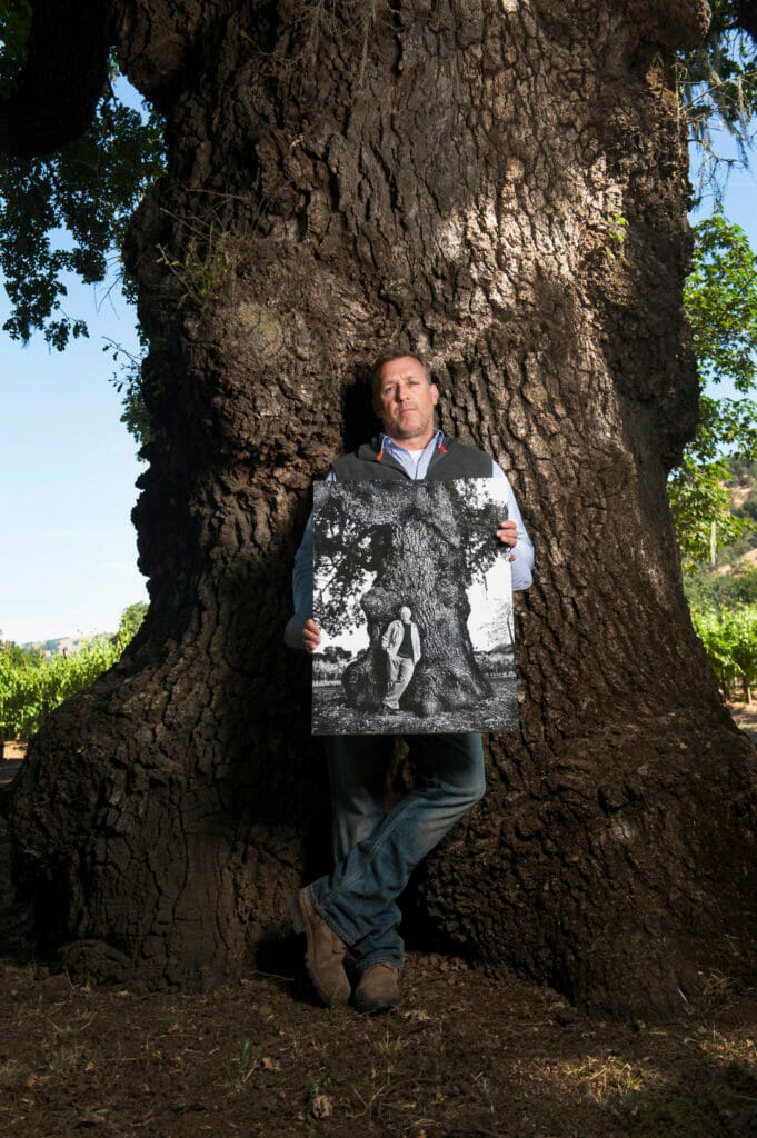Alexander Eiesle at the Volker Eisele Family Estate in St. Helenia with photograph of his father, the late Volker Eisele at same old Oak tree on the estate.